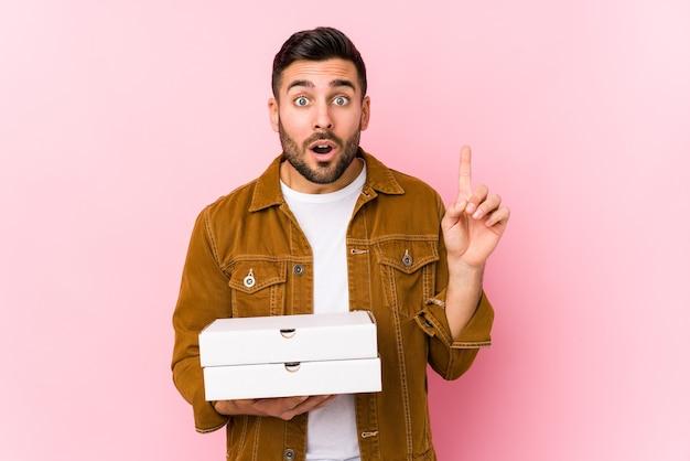 Jovem bonito segurando pizzas isoladas, tendo uma ótima ideia, o conceito de criatividade.