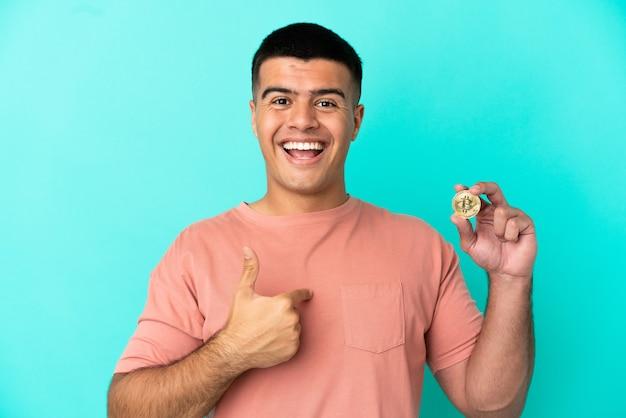 Jovem bonito segurando um bitcoin sobre um fundo azul isolado com expressão facial de surpresa