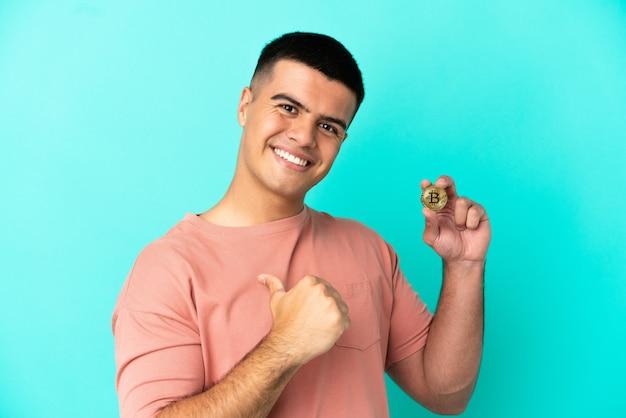 Jovem bonito segurando um bitcoin sobre um fundo azul isolado, orgulhoso e satisfeito
