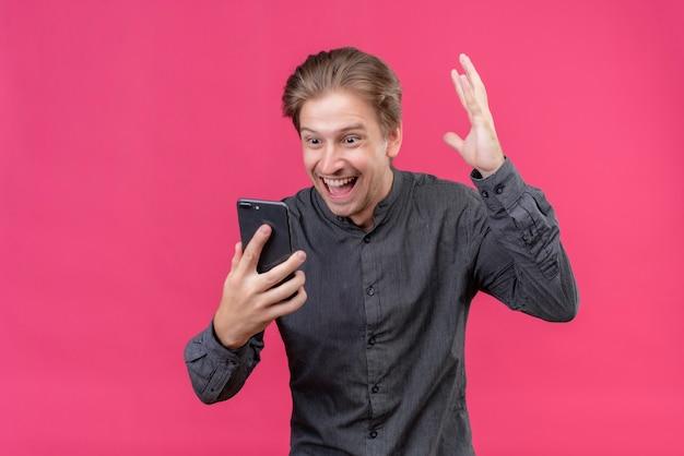 Jovem bonito segurando um celular feliz, sorrindo, levantando a mão