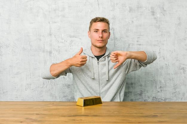 Jovem bonito segurando um lingote de ouro em uma mesa mostrando os polegares para cima e os polegares para baixo, difícil escolher