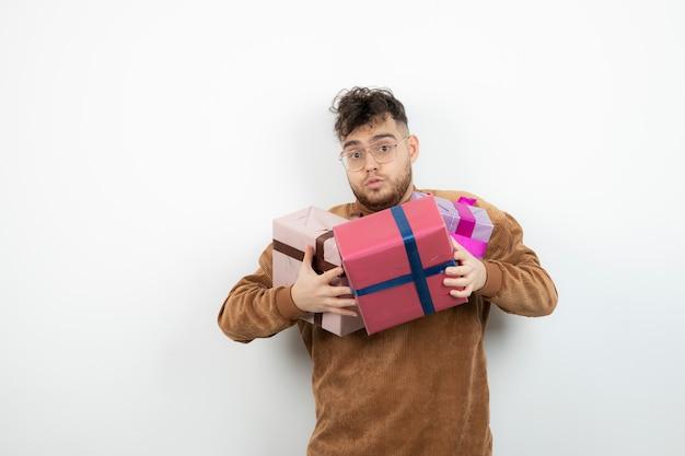 Jovem bonito segurando um monte de presentes
