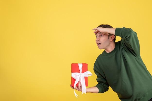 Jovem bonito segurando um presente de frente e olhando para algo amarelo