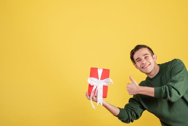 Jovem bonito segurando um presente de frente, fazendo o polegar para cima assinar em amarelo