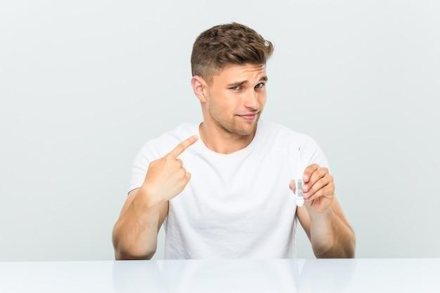Jovem bonito segurando um termômetro apontando com o dedo para você como se estivesse convidando se aproximar.