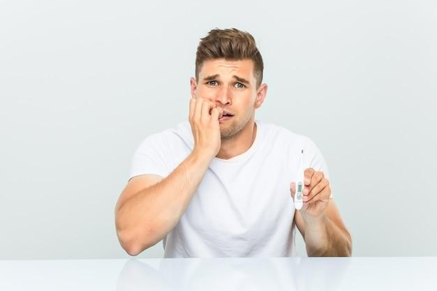 Jovem bonito segurando um termômetro roer unhas, nervoso e muito ansioso.