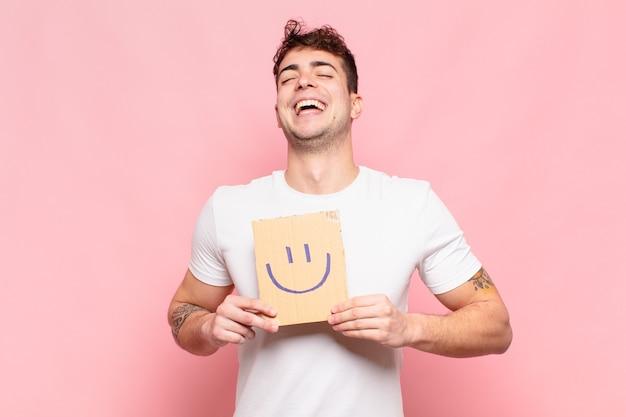 Jovem bonito segurando uma caixa com um sorriso