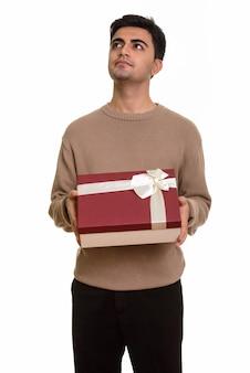 Jovem bonito segurando uma caixa de presente enquanto pensa