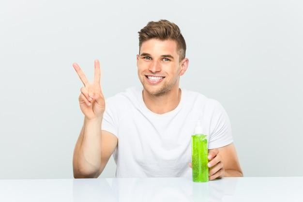 Jovem bonito segurando uma garrafa de aloe vera, mostrando o número dois com os dedos.