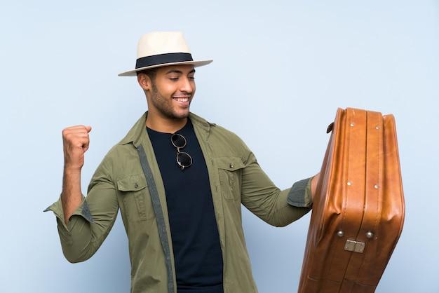 Jovem bonito, segurando uma mala vintage comemorando uma vitória