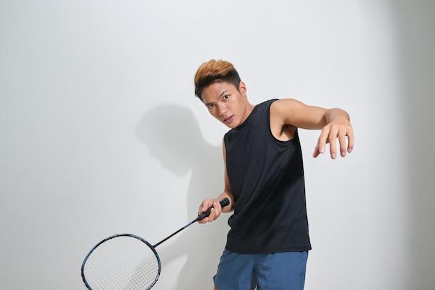 Jovem bonito segurando uma raquete de badminton e peteca cinza