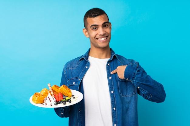 Jovem bonito segurando waffles sobre parede azul isolada com expressão facial de surpresa
