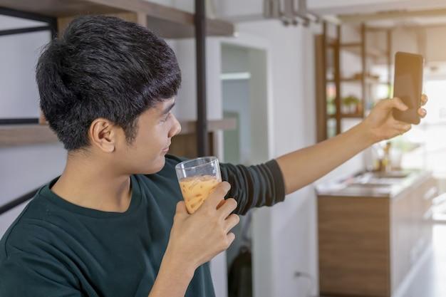 Jovem bonito selfie feliz na cozinha