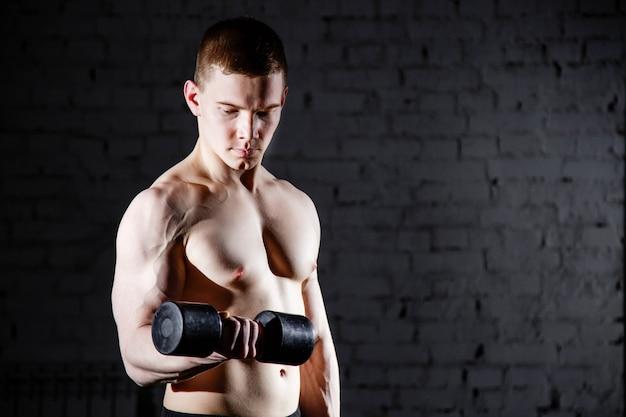 Jovem bonito sem camisa com corpo sexy musculoso fazendo exercícios usando halteres contra uma parede de tijolos.