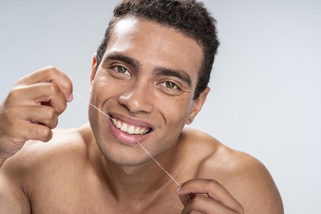 Jovem bonito sendo feliz passando fio dental
