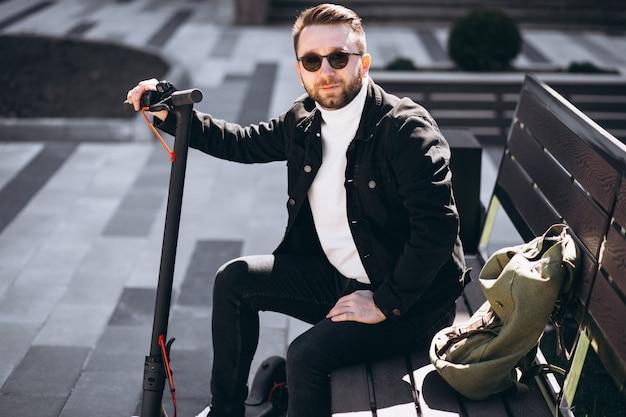 Jovem bonito sentado no banco do parque, descansando de um passeio de scooter