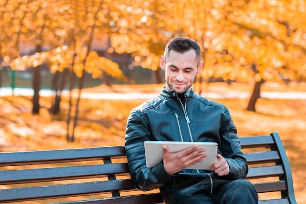 Jovem bonito sentado no banco e usando o big white tablet pc no beautiful autumn park