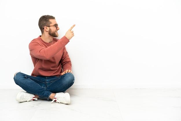 Jovem bonito sentado no chão apontando para trás com o dedo indicador