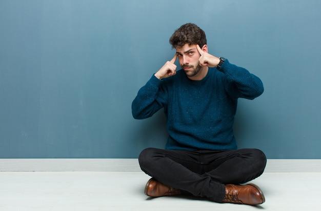 Jovem bonito sentado no chão com um olhar sério e concentrado, brainstorming e pensando em um problema desafiador