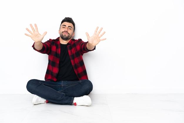 Jovem bonito sentado no chão contando dez com os dedos