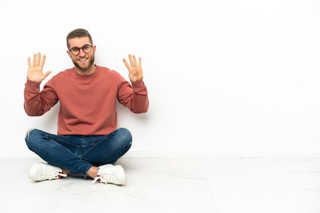 Jovem bonito sentado no chão contando nove com os dedos