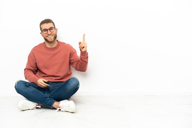 Jovem bonito sentado no chão mostrando e levantando um dedo em sinal dos melhores