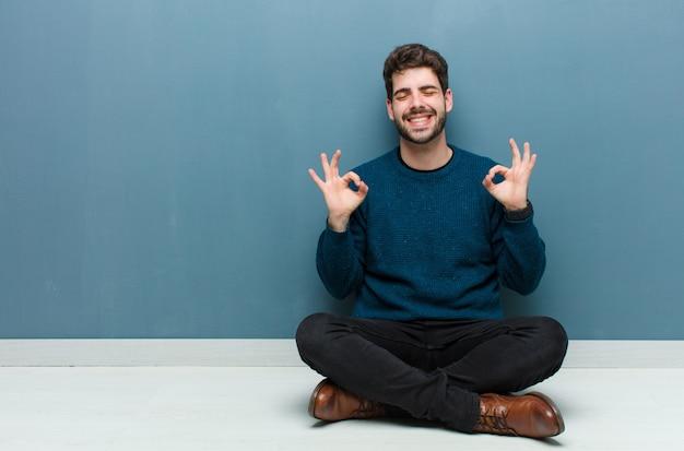 Jovem bonito sentado no chão olhando concentrado e meditando, sentindo-se satisfeito e relaxado, pensando ou fazendo uma escolha