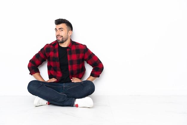 Jovem bonito sentado no chão, posando com os braços na cintura e sorrindo