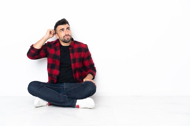 Jovem bonito sentado no chão tendo dúvidas e com expressão facial confusa