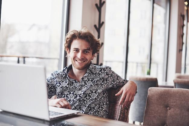 Jovem bonito sentado no escritório com uma xícara de café e trabalhando no projeto conectado com as modernas tecnologias cibernéticas