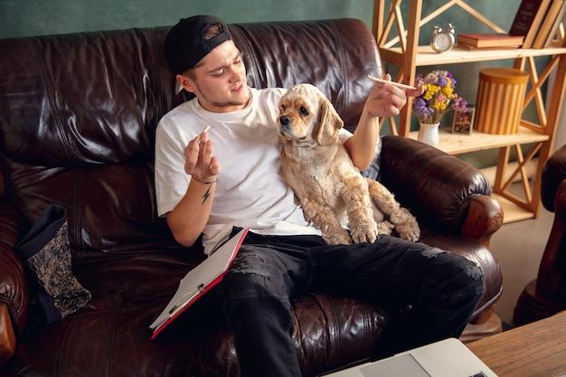 Jovem bonito sentado no sofá marrom e trabalhando com seu lindo cachorro