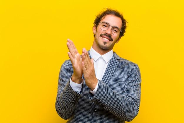 Jovem bonito, sentindo-se feliz e bem sucedido, sorrindo e batendo palmas de mãos, dizendo parabéns com um aplauso contra a parede laranja