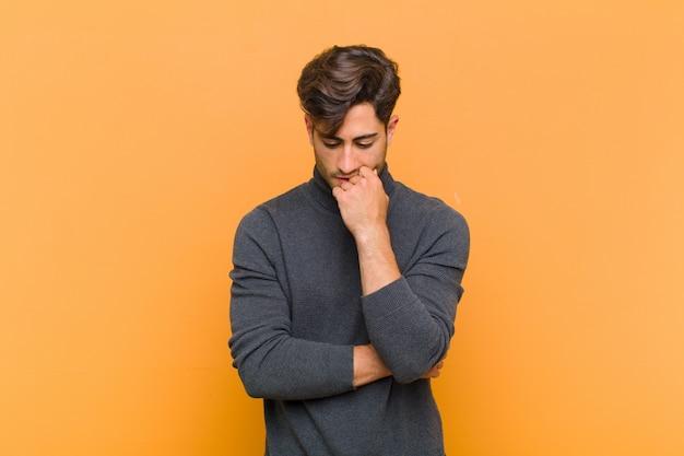 Jovem bonito, sentindo-se sério, pensativo e preocupado, olhando de soslaio com a mão pressionada sobre o queixo contra a parede laranja