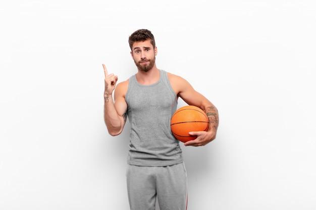 Jovem bonito, sentindo-se um gênio segurando o dedo orgulhosamente no ar depois de perceber uma ótima idéia, dizendo eureka segurando uma bola de basquete