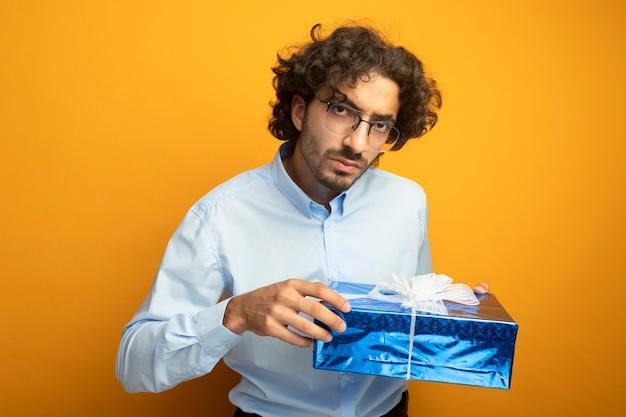Jovem bonito sério de óculos segurando um pacote de presente, olhando para a frente, isolado na parede laranja