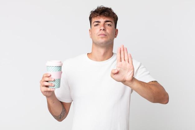Jovem bonito sério, mostrando a palma da mão aberta, fazendo gesto de pare e segurando um café para levar