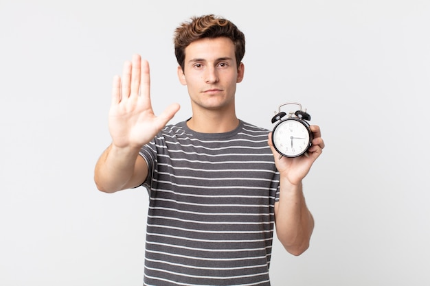 Jovem bonito sério, mostrando a palma da mão aberta fazendo gesto de pare e segurando um despertador
