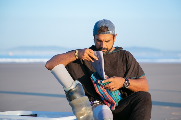 Jovem bonito sério sentado na praia e colocando uma prótese abaixo do joelho Foto gratuita