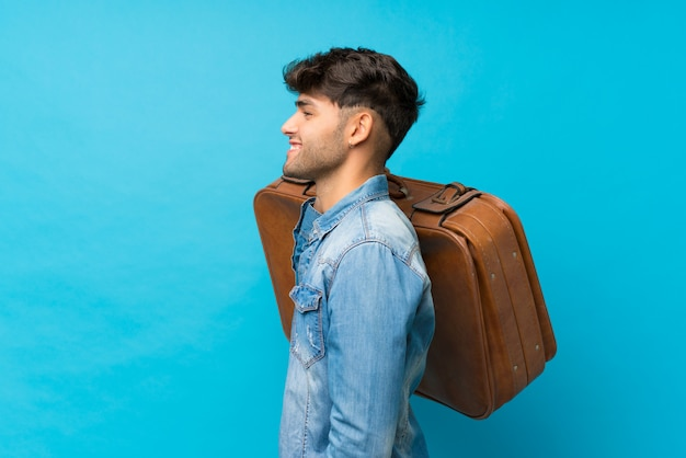 Jovem bonito sobre azul isolado, segurando uma mala vintage