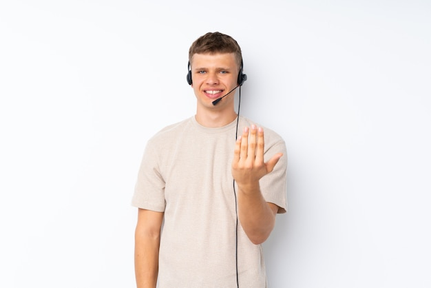 Jovem bonito sobre branco trabalhando com fone de ouvido fazendo gesto próximo