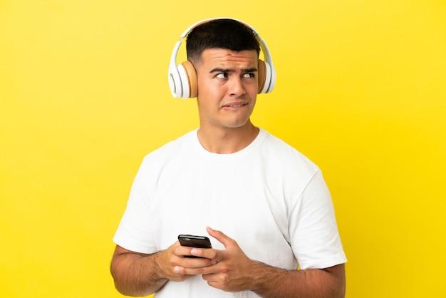 Jovem bonito sobre fundo amarelo isolado, ouvindo música com um celular e pensando