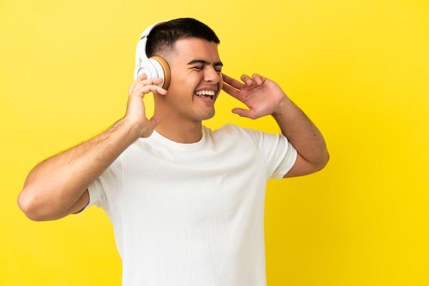 Jovem bonito sobre fundo amarelo isolado ouvindo música e cantando