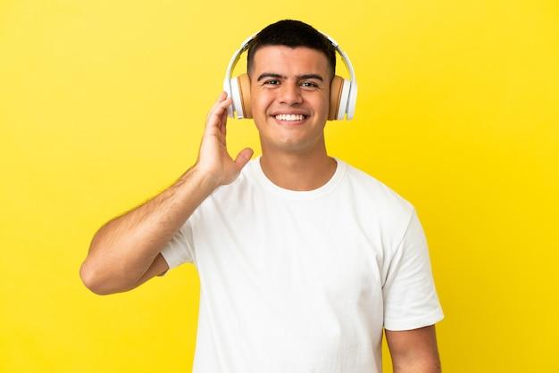 Jovem bonito sobre fundo amarelo isolado ouvindo música