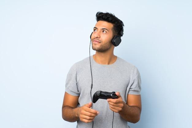 Jovem bonito sobre fundo isolado, jogando em videogames