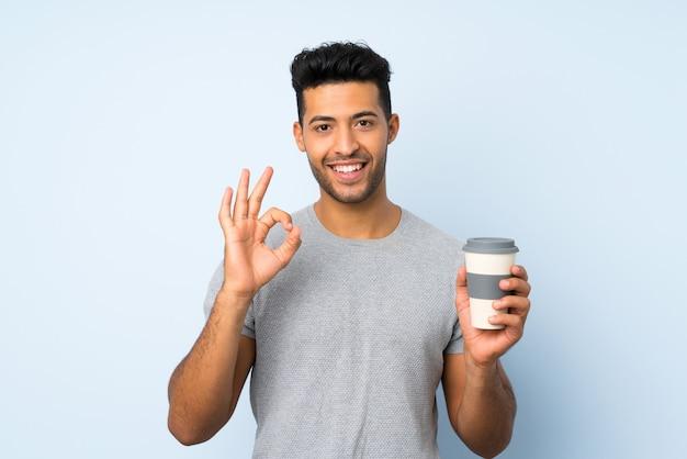 Jovem bonito sobre fundo isolado, segurando o café para levar embora fazendo sinal de ok