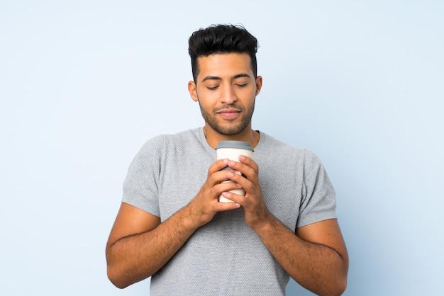 Jovem bonito sobre fundo isolado, segurando o café para levar
