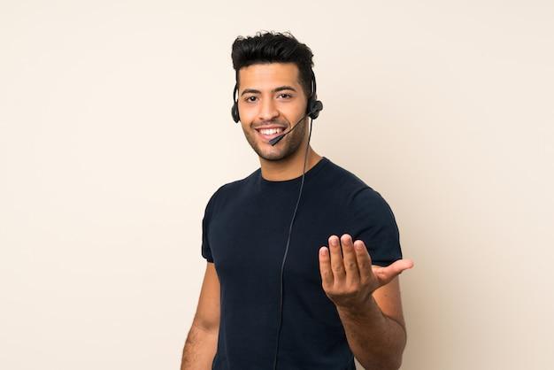 Jovem bonito sobre fundo isolado, trabalhando com fone de ouvido fazendo o próximo gesto