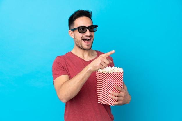 Jovem bonito sobre parede azul isolada com óculos 3d e segurando um grande balde de pipocas enquanto apontando para fora