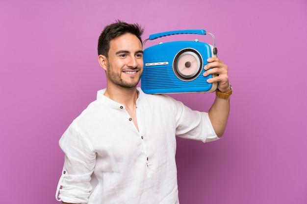 Jovem bonito sobre roxo segurando um rádio