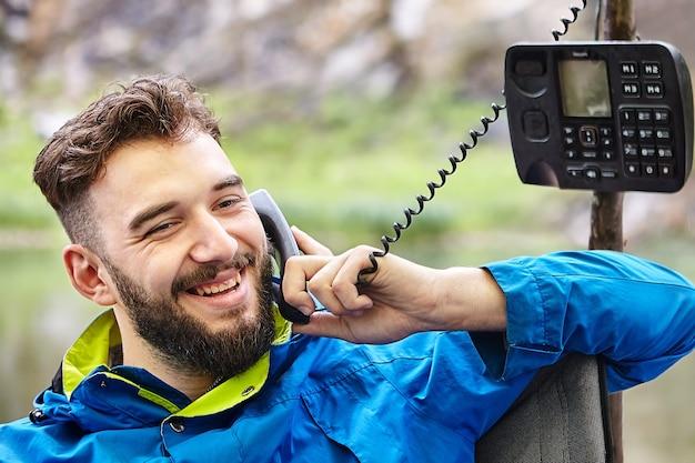 Jovem bonito sorri durante uma agradável conversa telefônica na natureza, usando um telefone com botão de pressão desatualizado com fio trançado.